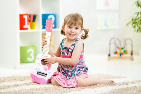 kids dress: little girl with guitar toy gift siiting on floor Stock Photo