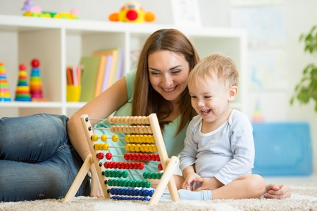 kid and his mother playing with abacus photo