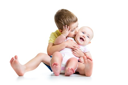 Loving brother kissing his little sister isolated on white photo