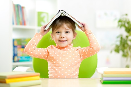 preschooler  kid girl with book over her head indoors photo
