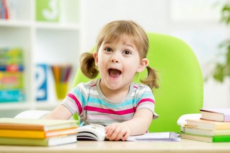 Happy kid girl reading book at table in nursery Stockfoto
