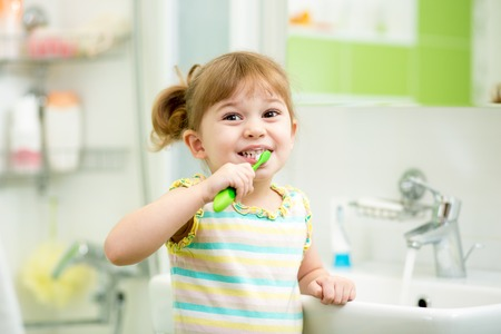 kd girl brushing teeth in bath room photo