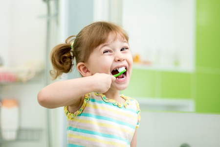 Funny child girl brushing teeth in bathroom Stock Photo