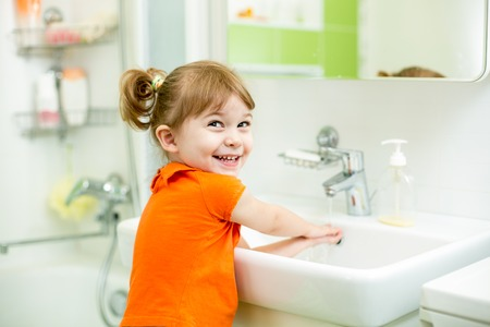 Cute kid girl washing in bath room photo