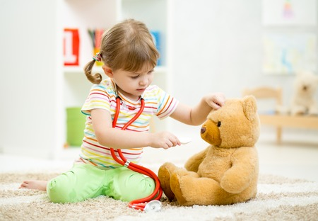 child girl playing doctor and curing plush toy indoors photo