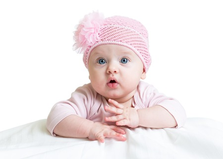 baby girl in pink knitted hat lying on white bed photo