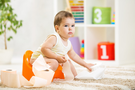 kid boy sitting on chamber pot with toilet paper roll Stock Photo