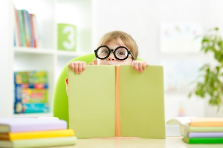 clever little child behind of open book indoor photo