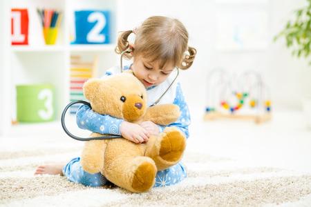 Söt unge flicka som leker doktor med plysch leksak hemma