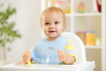happy baby kid boy waiting for food with spoon at table