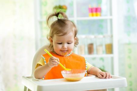 niños desayunando: linda chica niño comer alimentos en la cocina