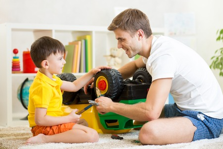 kid boy and his father repair toy trunk