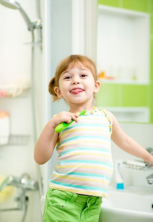 Funny child girl brushing teeth and tongue in bathroom photo
