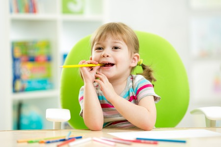 thoughful child girl drawing with colorful pencils photo