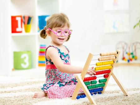 jong meisje met bril spelen abacus speelgoed