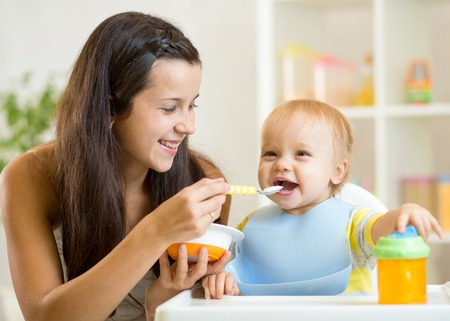 Happy mother spoon feeding baby child at home photo