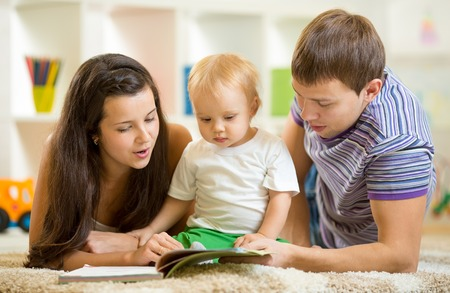 Young happy family with baby boy read children book laying on floor photo