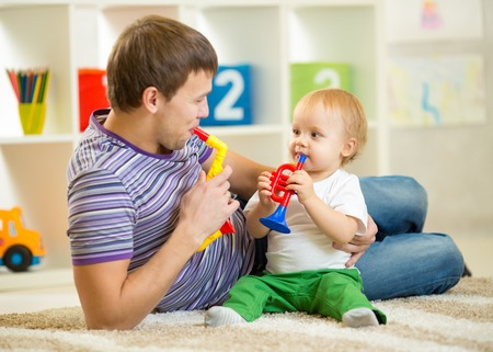 Happy family dad and son play musical toys on floor photo