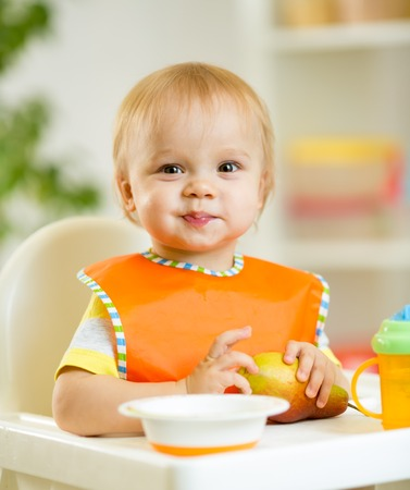happy cute baby kid toddler eating itself with spoon photo
