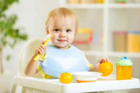 smiling cute child baby boy eating itself with spoon Stock Photo