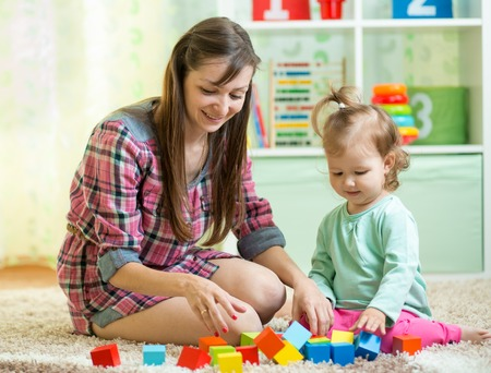 mother with his child play together at home photo