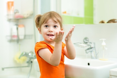 Cute child girl washing hands in bathroom