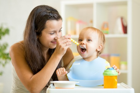 Beautiful young woman feeds child baby boy photo