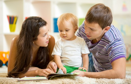 three story: Young happy family with baby son read children book laying on floor