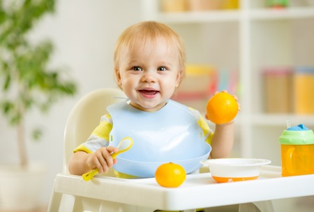 happy baby kid child boy eating healthy food at home Banque d'images