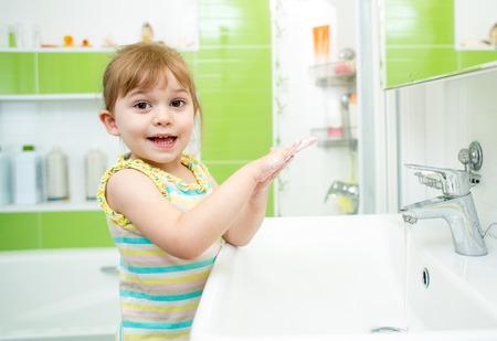Cute kid girl washing in bath room photo