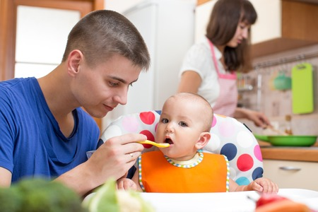 father feeding his baby girl and mother cooking at kitchen photo