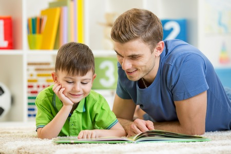 kid boy and his father read a book on floor indoors photo
