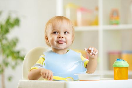 glimlachende schattige baby jongen jongen zelf eten met lepel