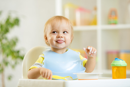 baby chair: smiling cute baby kid boy eating itself with spoon