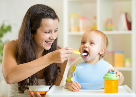 Happy mum spoon feeding child son indoor photo