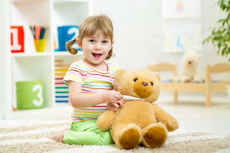 child girl playing doctor with plush toy at nursery photo