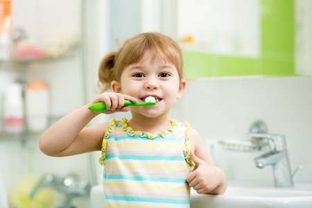 Cute child girl brushing teeth in bathroom
