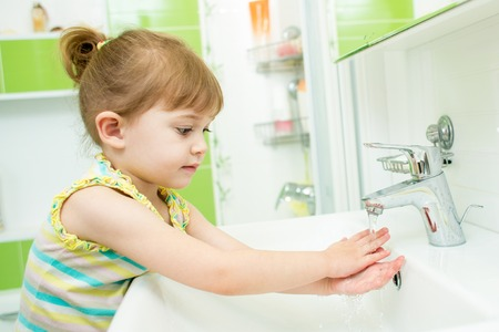 Cute little girl washing hands in bathroom Banque d'images