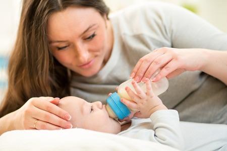 teteros: hermosa madre de alimentación de bebé con una botella de leche en el país
