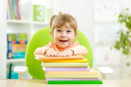 Cute kid girl preschooler with books in elementary school photo