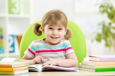 Happy child girl reading book at table in nursery photo