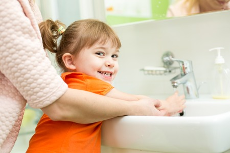 mother washing kid girl hands in bathroom Stock Photo