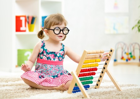 child kid weared glasses playing with abacus toy indoor Stock Photo