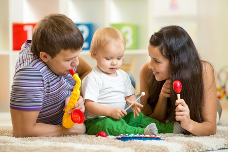Happy family play musical toys at home photo
