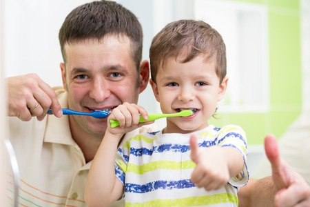 dad and child boy brushing teeth in bathroom photo