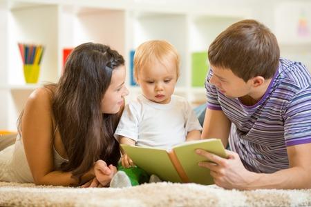 mujer leyendo libro: Los padres j�venes mam� y pap� los ni�os la lectura de libros a hijo beb� Foto de archivo