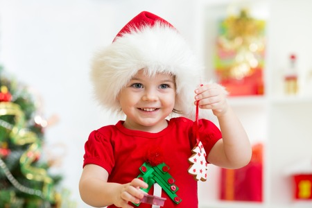 little girl in Santa hat holding Christmas biscuits photo