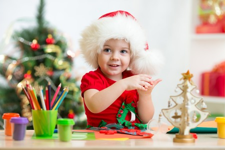 making: child girl in Santa hat making christmas tree of plasticine Stock Photo
