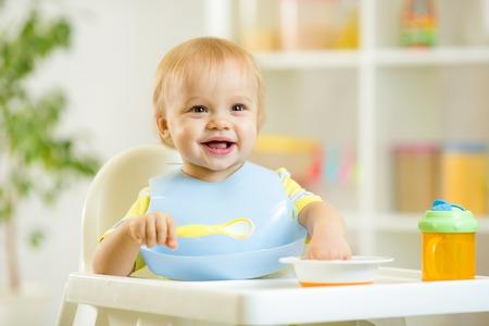gelukkig schattige baby jongen jongen eten dood zelf met lepel Stockfoto