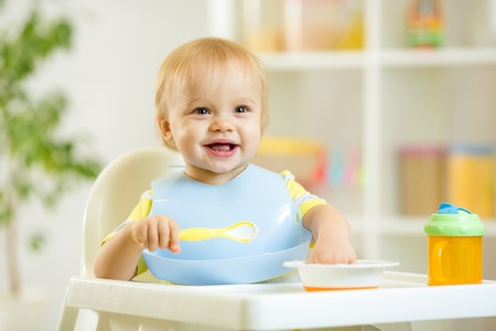 happy cute baby kid boy eating dood itself with spoon Stock Photo - 33584529